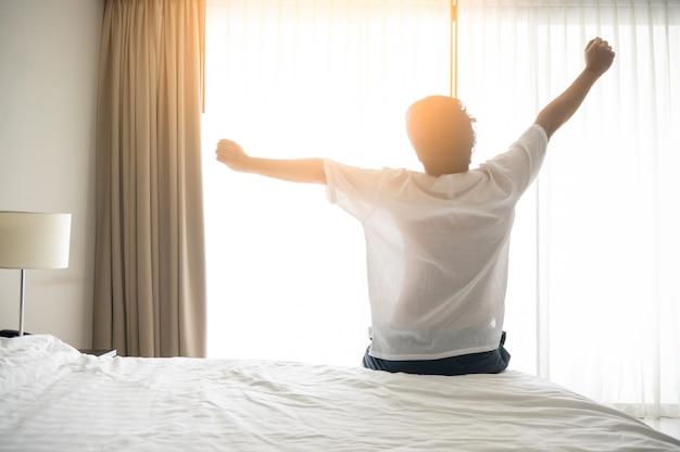 L'uomo si sveglia e si allunga al mattino con la luce del sole