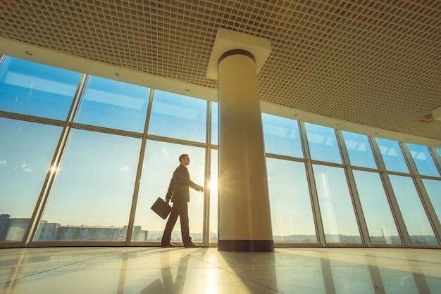 L'uomo cammina con una valigia nel corridoio dell'ufficio