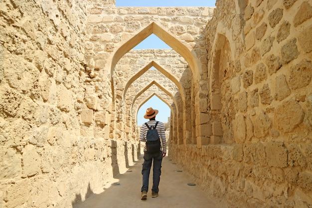 Uomo che cammina lungo gli iconici archi nel forte del bahrain, manama, bahrain