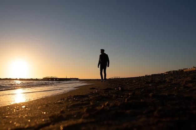 Uomo che cammina sulla spiaggia e guarda il tramonto sul mare