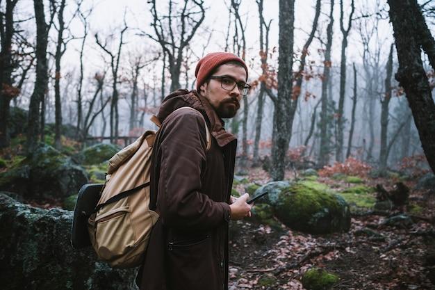 Uomo che cammina su un sentiero buio attraverso una foresta spettrale. hipster con uno zaino dietro la schiena va in viaggio