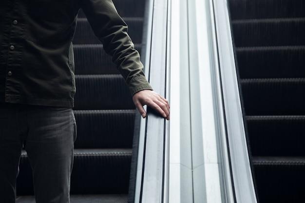 Un uomo che cammina lungo la scala mobile d'acciaio nella metropolitana