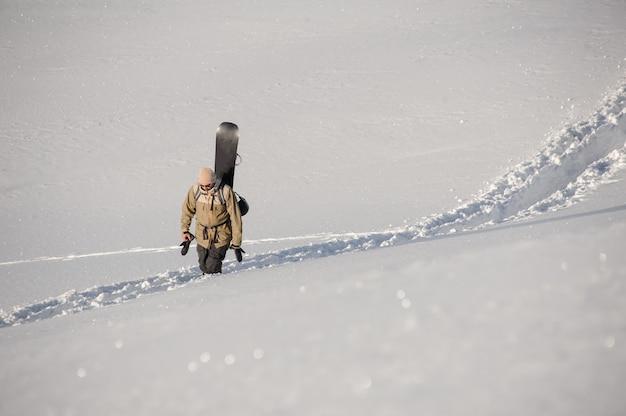 Uomo che cammina sul sentiero calpestato nella neve con lo snowboard dietro la schiena nella famosa località turistica di gudauri in georgia