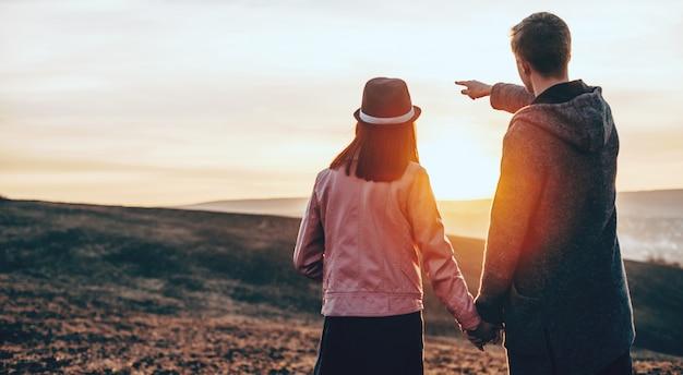 L'uomo che cammina mano nella mano in un campo con la sua donna sta indicando il paesaggio