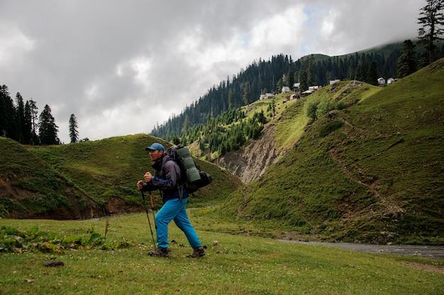 Uomo che cammina sulla collina con zaino e bastoncini da trekking