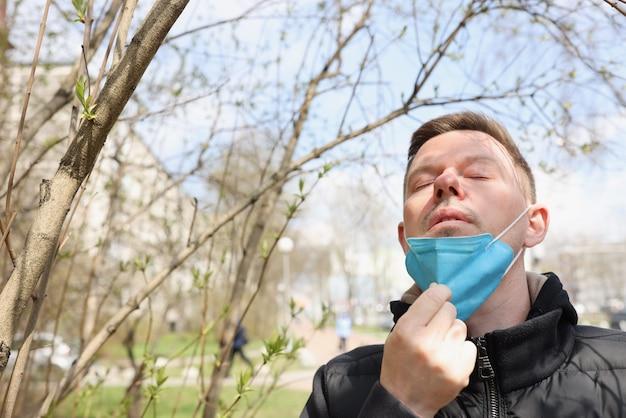 Uomo che cammina nel parco e togliendosi la maschera protettiva dal viso