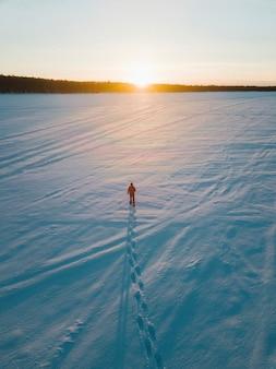 Uomo che cammina sulla neve ammirando il tramonto