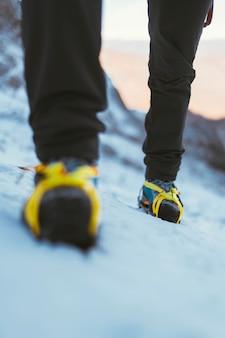 Uomo che cammina nella neve con i ramponi