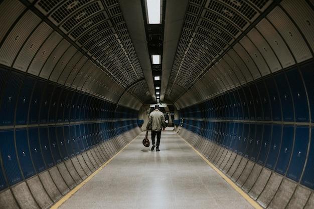 Uomo che cammina nel tunnel sotterraneo