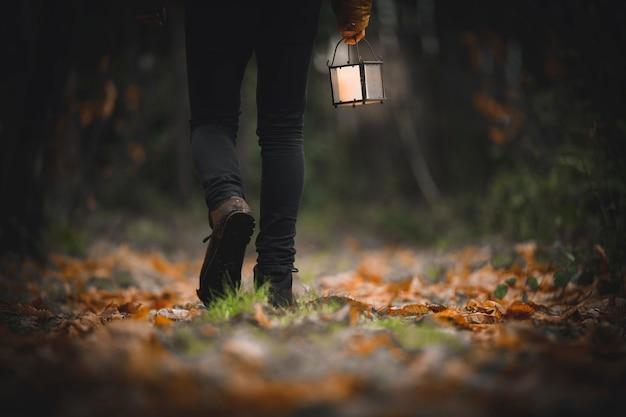 Uomo che cammina con una lanterna in un bosco