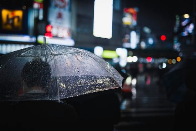 Uomo che cammina con un ombrello trasparente in una città di notte