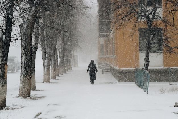 Un uomo cammina lungo una strada innevata. tempesta di neve sulla strada.