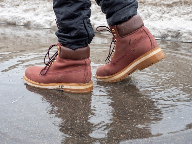 Un uomo cammina attraverso una pozzanghera con scarpe di cuoio di terracotta. primo piano, riflesso in una pozzanghera, orizzonte disseminato. concetto di uomo che cammina, viaggio, vista laterale