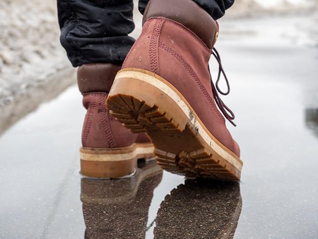 Un uomo cammina attraverso una pozzanghera con scarpe di cuoio di terracotta.