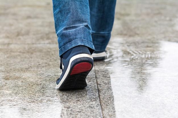 Un uomo cammina in una pozzanghera