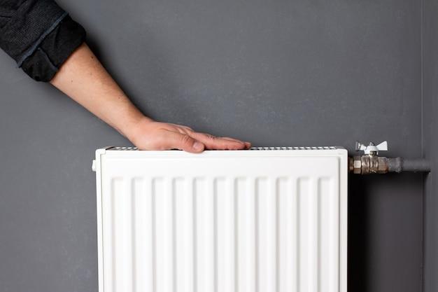 Uomo che scalda le mani sul radiatore di riscaldamento vicino al muro grigio, primo piano