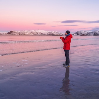 Un uomo si riscalda con il tè. tè caldo sulla costa artica fredda e deserta.