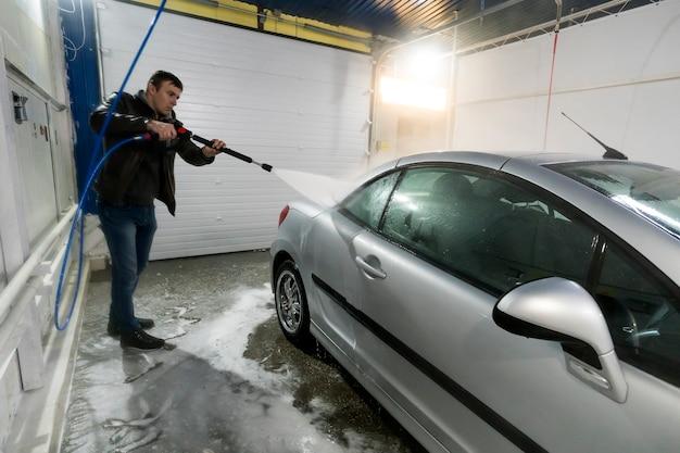 Un uomo lava un'auto in una scatola di autolavaggio senza contatto self-service con una pistola ad acqua in una stazione di lavaggio self-service manuale. il lavoratore di sesso maschile lava l'auto con un'idropulitrice