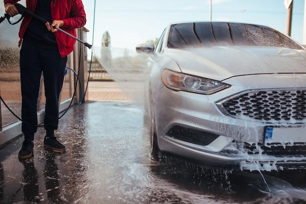 Un uomo lava un'auto con una pistola in un autolavaggio self-service