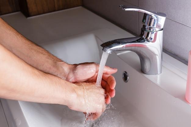 L'uomo si lava le mani vicino al lavabo bianco