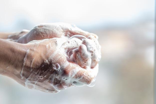 Un uomo si lava le mani con il sapone. mani degli uomini in una schiuma con bolle. trattamento. disinfezione delle mani. coronavirus hygiene rules