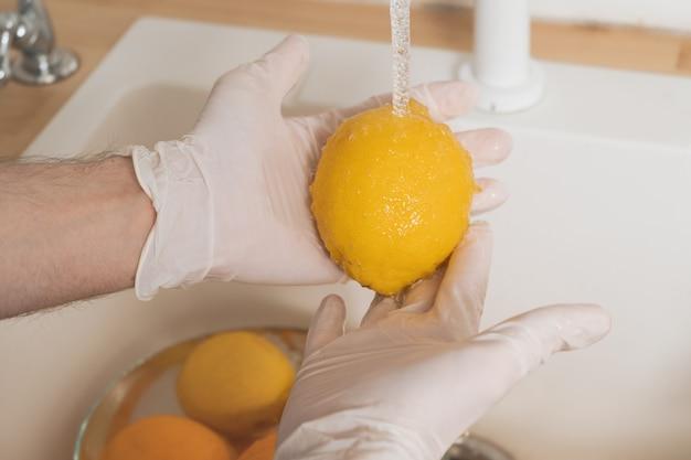 Un uomo lava un limone con un detersivo in guanti. un giovane sterilizza frutta e verdura durante un'epidemia. mani in primo piano guanti usa e getta lavare un limone sotto l'acqua corrente.