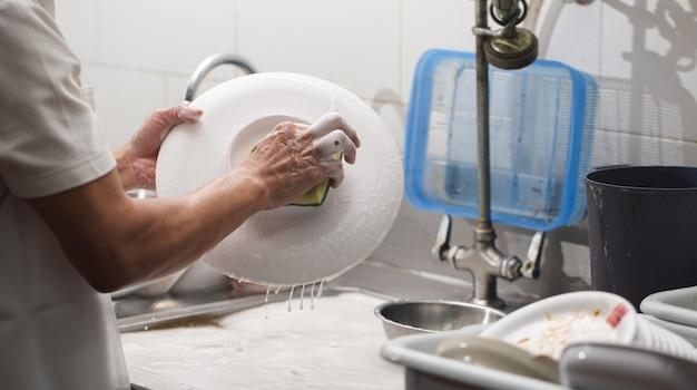 Uomo che lava piatto sul lavandino al ristorante
