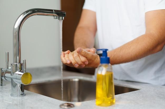Uomo che si lava le mani con il sapone in un lavandino a casa sua