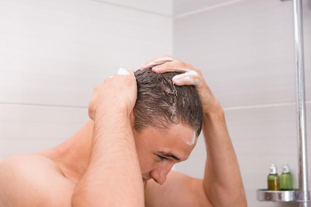 Uomo che si lava i capelli bagnati e gocciolanti nella cabina della doccia in bagno