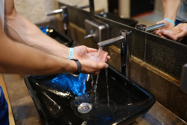 Uomo che si lava le mani sotto l'acqua corrente dal rubinetto nel primo piano del bagno pubblico