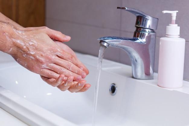Uomo che si lava le mani in acqua corrente, in un bagno pubblico.