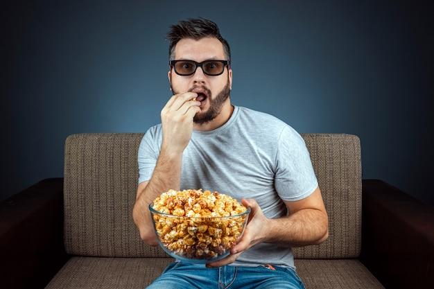 Un uomo guarda un film o una serie con occhiali 3d, una parete blu. il concetto di cinema, film, emozioni, sorpresa, tempo libero, piattaforme di streaming.