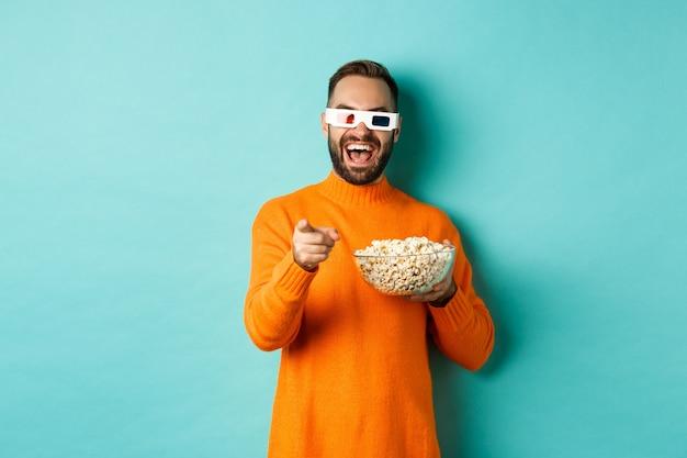 Uomo che guarda la commedia in occhiali 3d, mangia popcorn, ride e indica lo schermo della telecamera, in piedi su sfondo blu.