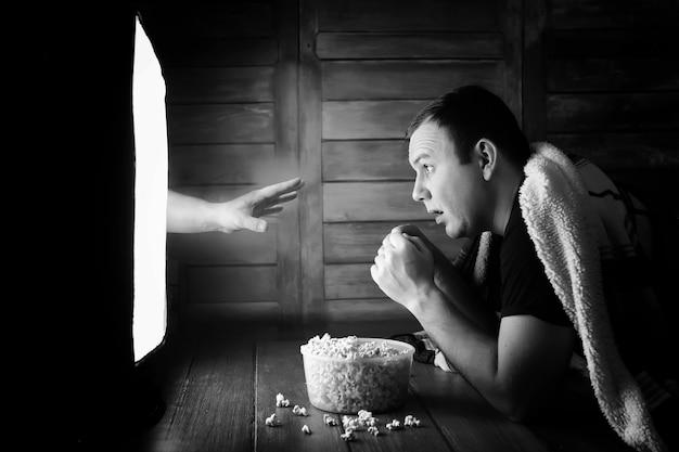 Un uomo che guarda un film dell'orrore in tv in bianco e nero