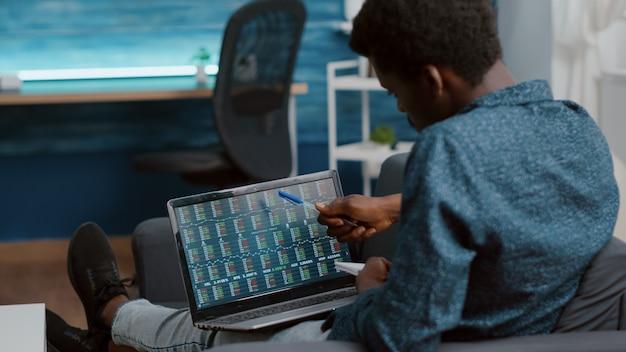 Uomo che guarda e monitora i mercati azionari delle valute crittografiche che controllano l'indice ticker azionario, decidendo di acquistare o vendere moneta digitale