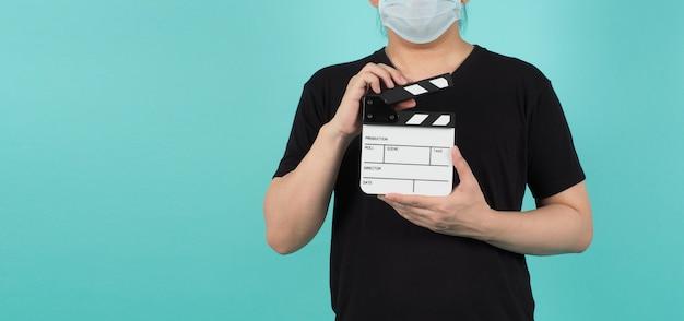 L'uomo indossa una maschera per il viso e tiene in mano il ciak o l'ardesia del film. utilizza nella produzione di video e nell'industria cinematografica su sfondo verde o menta o blu tiffany. indossa una maglietta nera.