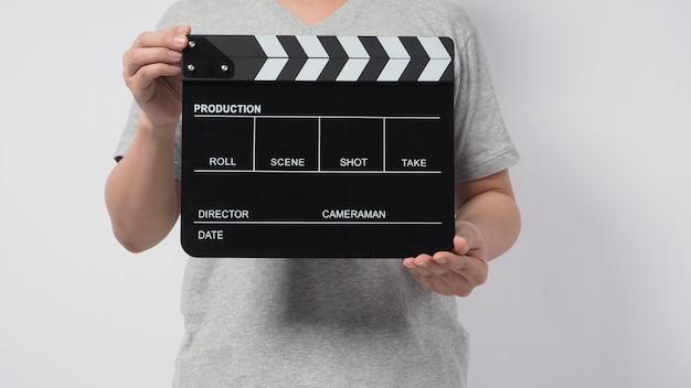 Un uomo indossa una maglietta grigia e la mano tiene in mano un batacchio nero o una lavagna per film. utilizza nella produzione video o nell'industria cinematografica. è uno sfondo bianco.