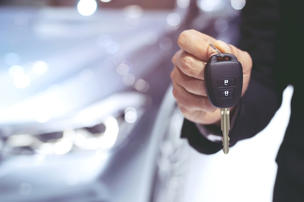 L'uomo indossa la mano di giacca di pelle che tiene un pulsante sul telecomando delle chiavi dell'auto contro il tavolo della macchina sfocatura