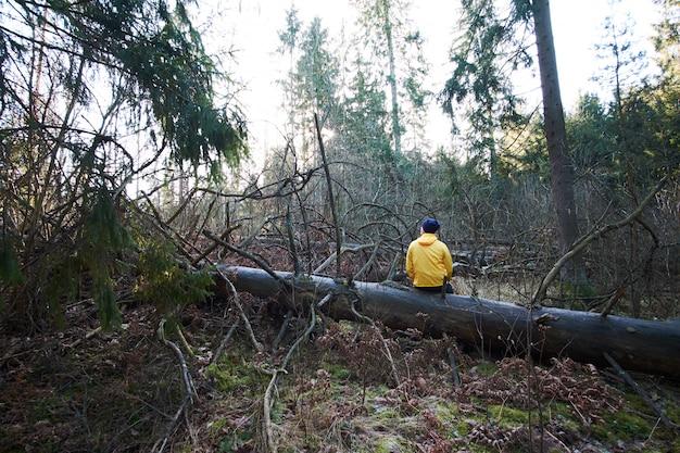 L'uomo indossava un impermeabile giallo seduto su un tronco enorme e rilassante nella foresta