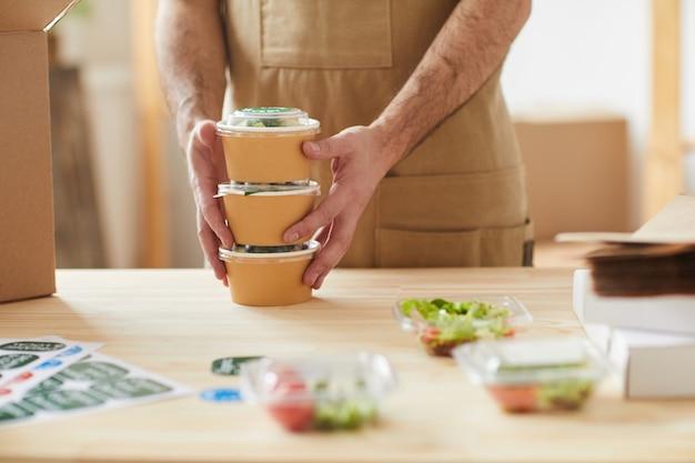 Uomo che indossa ordini di imballaggio grembiule mentre è in piedi da tavoli di legno, addetto al servizio di consegna di cibo