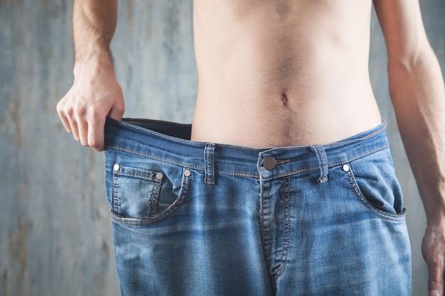 Uomo che indossa jeans di grandi dimensioni. perdita di peso