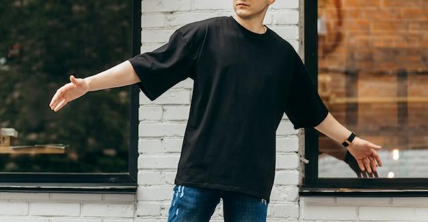 Uomo che indossa una maglietta nera vuota con spazio per il tuo logo o design mock up