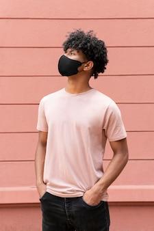 Uomo che indossa una maschera nera a scatto medio