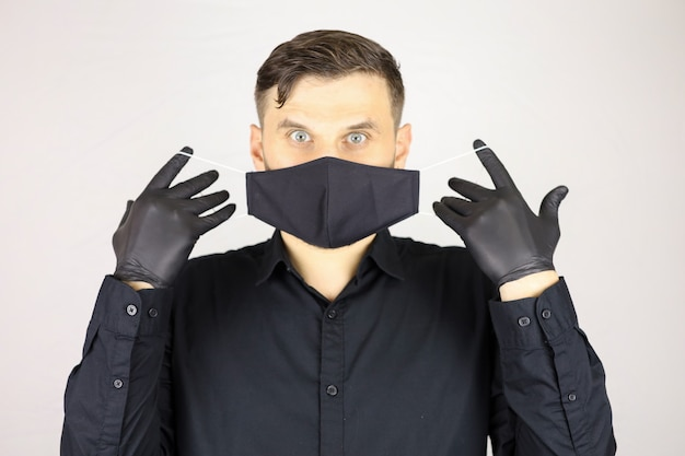 Un uomo che indossa guanti medicali neri rimuove una maschera protettiva su uno sfondo bianco