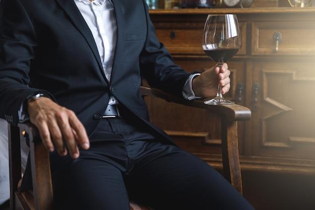 Uomo che indossa un abito nero con un bicchiere di vino rosso