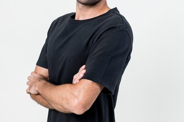 Uomo che indossa una maglietta nera con le braccia incrociate