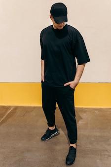 Uomo che indossa una maglietta nera e un berretto da baseball nero con uno sfondo a parete all'aperto