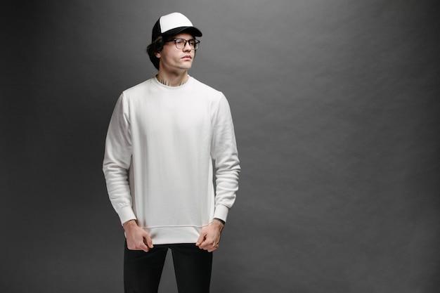 Uomo che indossa felpa bianca vuota e berretto da baseball vuoto in piedi su grigio