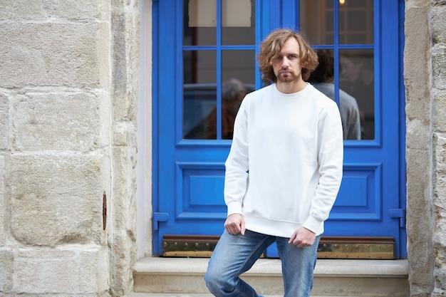 Uomo che indossa una felpa bianca vuota. felpa o felpa con cappuccio per mock up, design del logo o stampa di design con spazio libero.