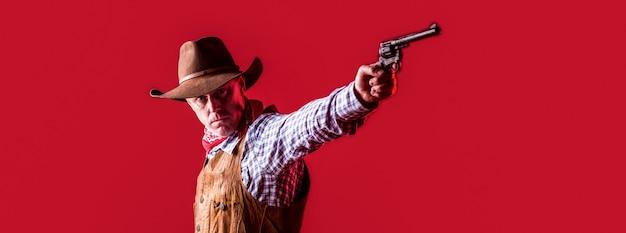 Uomo che indossa cappello da cowboy, pistola. ovest, pistole. ritratto di un cowboy. owboy con arma su sfondo rosso.